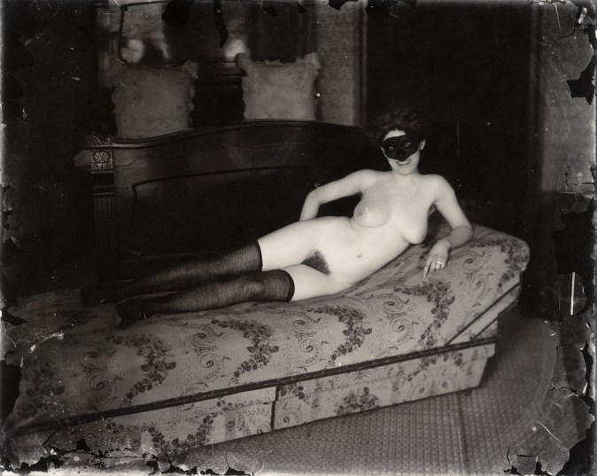 Black-and-white photograph of a nude woman wearing a mask laying on a sofa