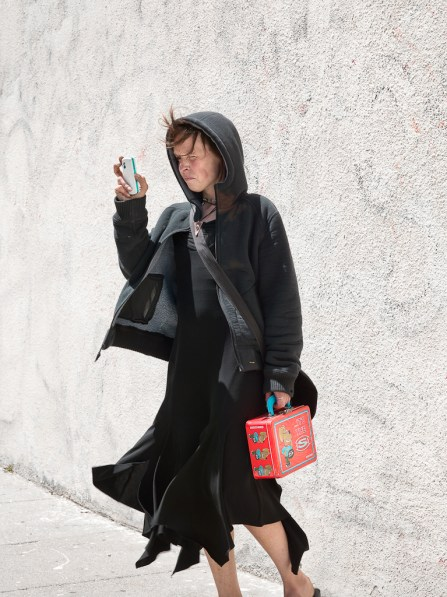Color photograph of a woman dressed all in black peering at a cellphone and holding a red lunchbox
