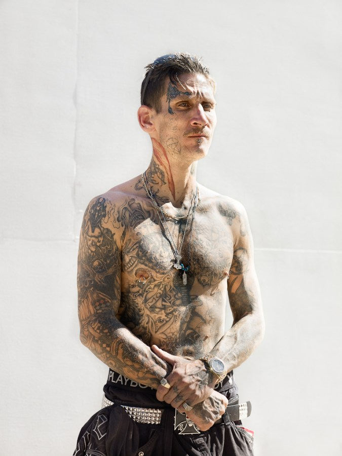 Color photograph of a shirtless tattooed man standing in front of a blank white wall