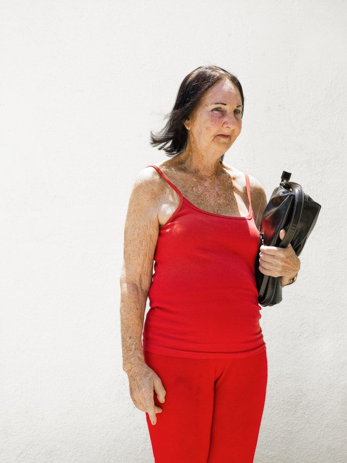 Color photograph of a woman wearing bright red holding a black purse under one arm