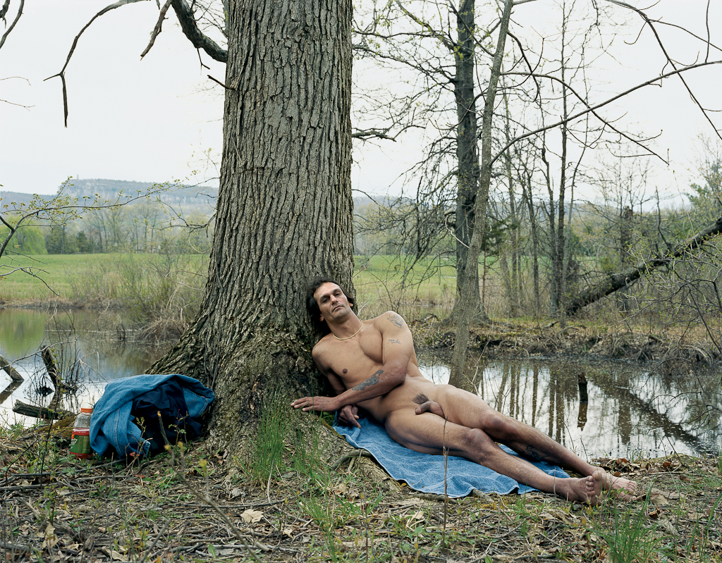 Color photograph of a nude man reclining against a tree next to a stagnant pond