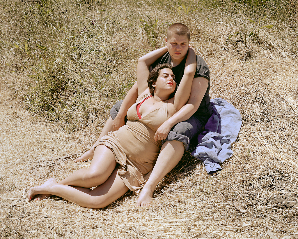 Color photograph of a couple in each other's arms reclining in a patch of long dry grass