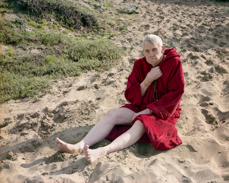 Color photograph of an elderly man seated on a sandy beach clutching a string of wooden beads and wrapped in a red towel