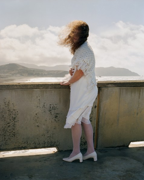 Color photograph of a woman with hair in her face in a white dress standing by a low wall overlooking the coast