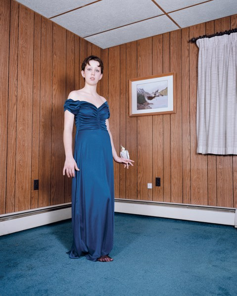 Color photograph of a woman in a long blue dress standing in the corner of a wood paneled room with a parakeet on one hand
