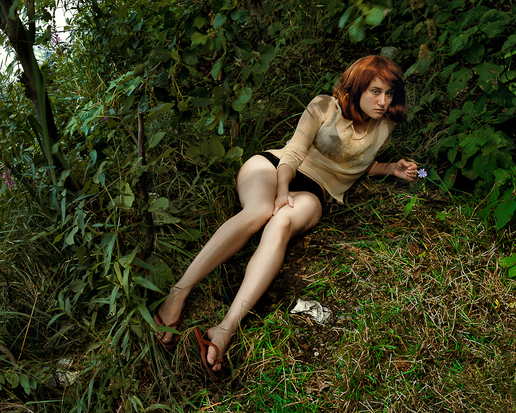 Color photograph of a red-haired woman seated amid grassy underbrush holding a flower in one hand