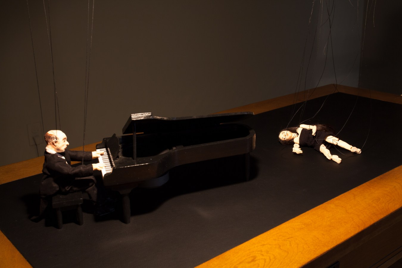 Close up of a marionette playing the piano and a dancer marionette on a desktop