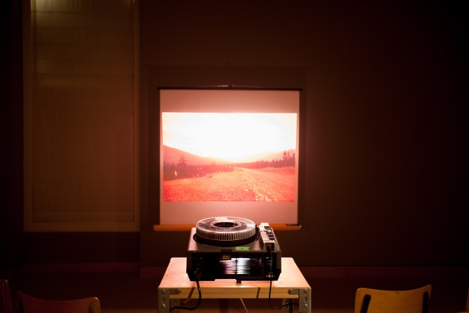 A slide projector projects an image of a landscape onto a screen in a darkened room