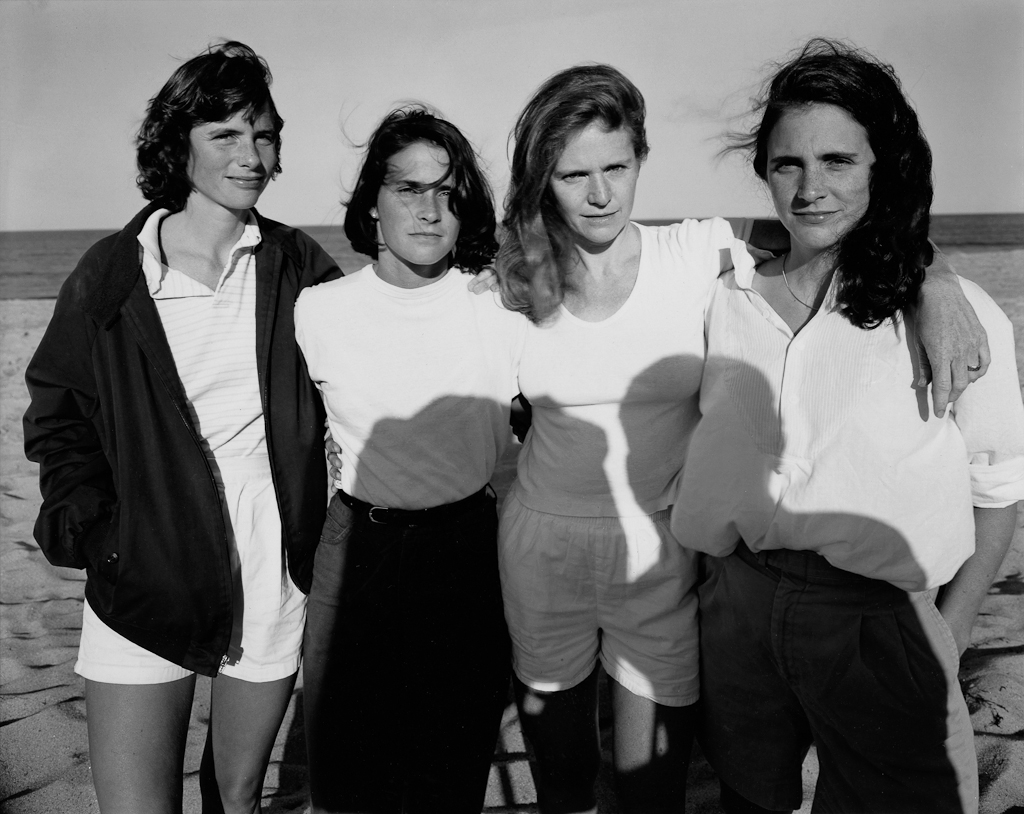 Black-and-white photographic portrait of four young women standing on a sunny beach with the ocean on the horizon