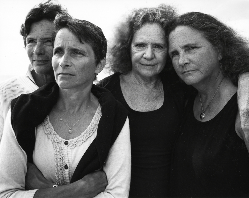 Black-and-white photographic portrait of four middle-aged women with two looking into the distance and two looking at the viewer