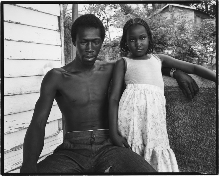 Black-and-white photograph of a seated young shirtless man with his arm around a standing young girl in a light-colored dress on a porch