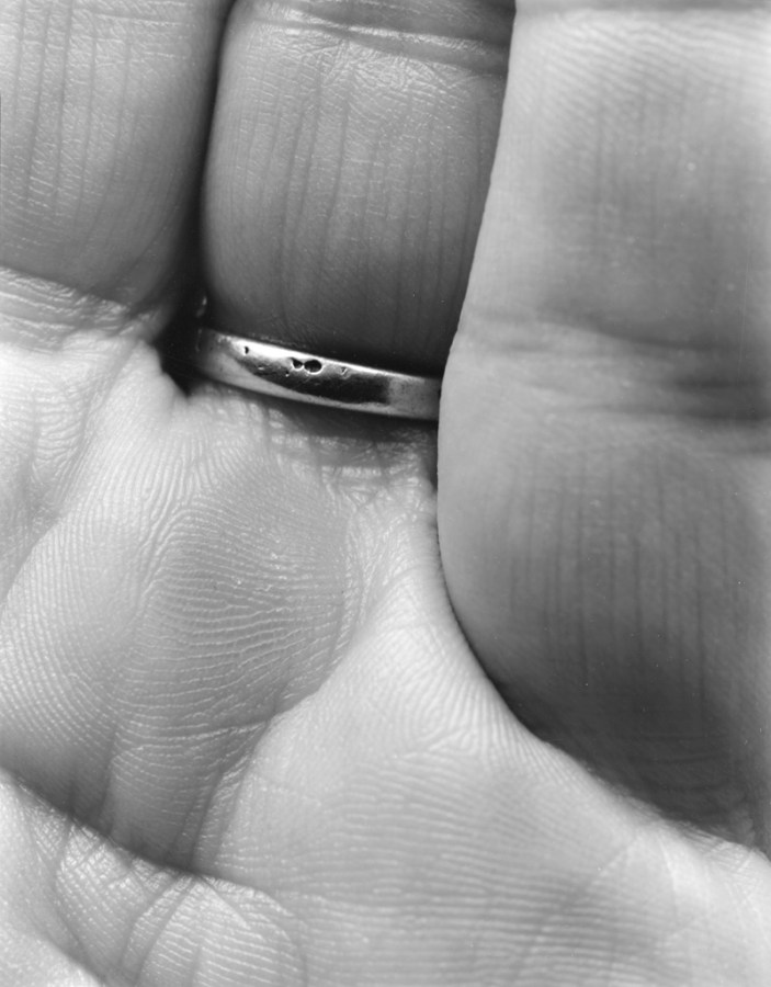 Black-and-white close-up photograph of of the inner base of three fingers, one wearing a ring