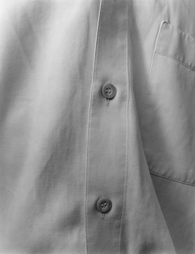 Black-and-white close-up photograph of the buttons of a shirt