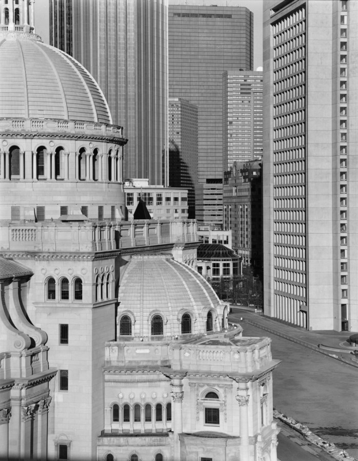 Black-and-white photograph of a domed church building against a background of modern high-rise building
