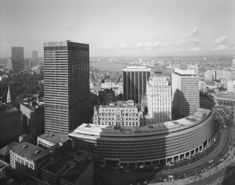 Black-and-white photograph of a curved building amid taller rectangular high-rise buildings