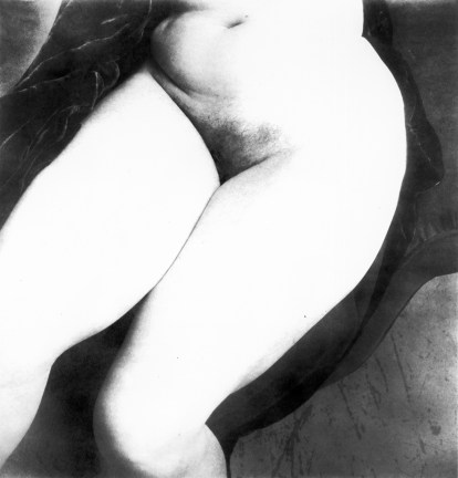 Black-and-white photograph of a nude woman's abdomen and thighs
