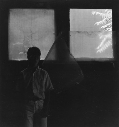 Black-and-white photograph of a person in shadow standing in front of two small windows