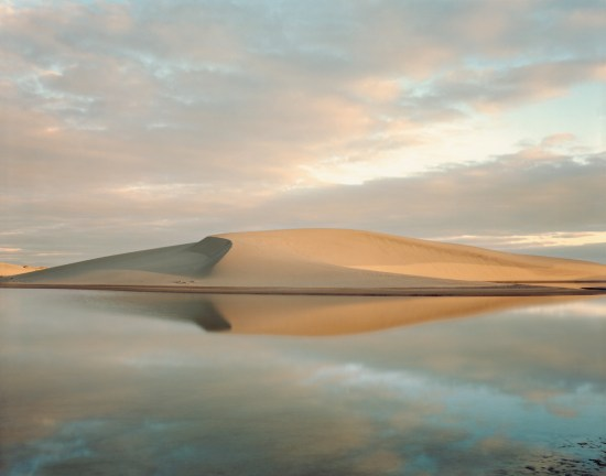 Color photograph of a desert dune above a still body of water