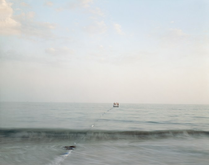Color photograph of four people drifting towards the horizon on a raft on a calm sea