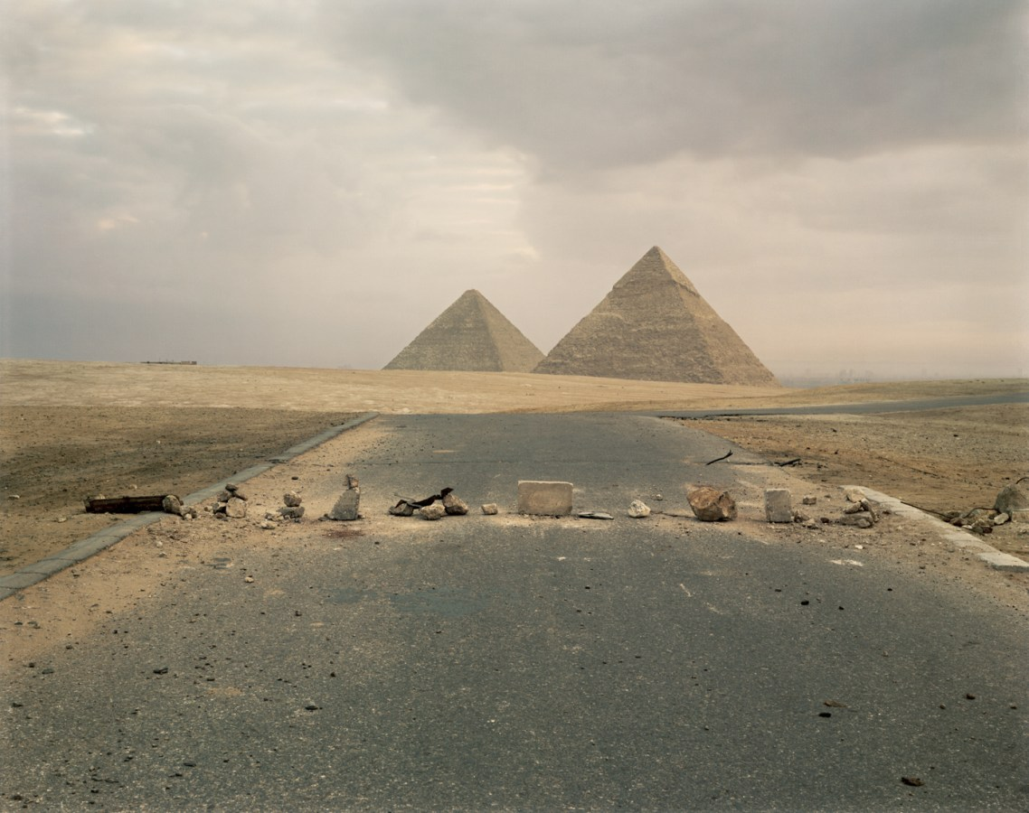 Color photograph of scattered rocks and blocks across a road leading towards two pyramids on the horizon