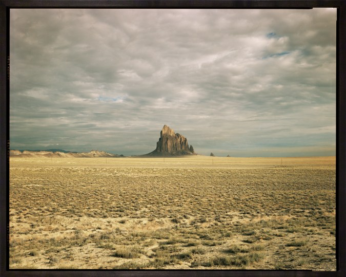 Color photograph of a monadnock in a desert landscape