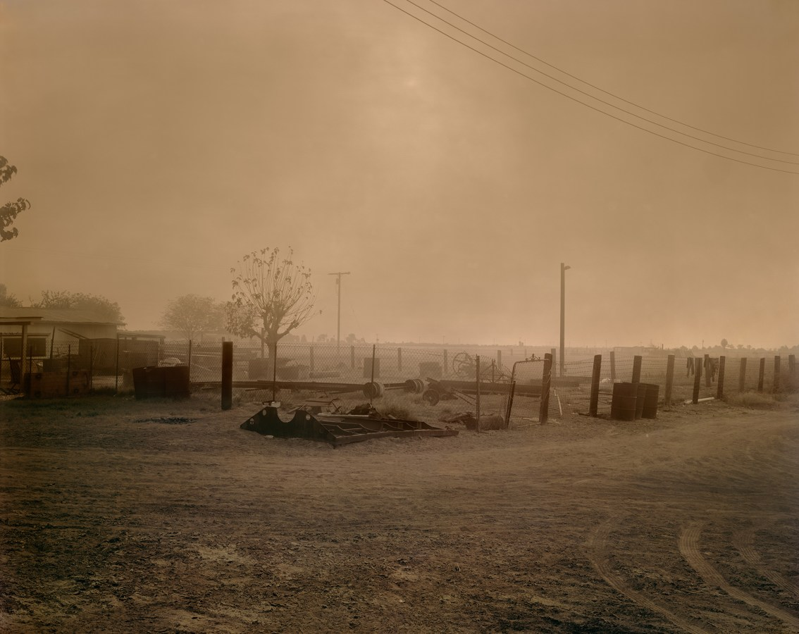 Color photograph of a smoke-filled sky above a fenced-in house and fields