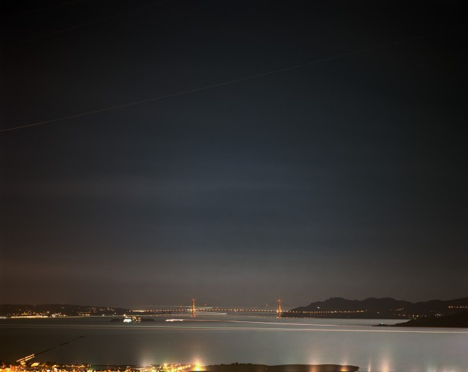 Long-exposure color photograph of the distant Golden Gate Bridge lit up at night with city skyline lights and moving light trails of boats in the foreground