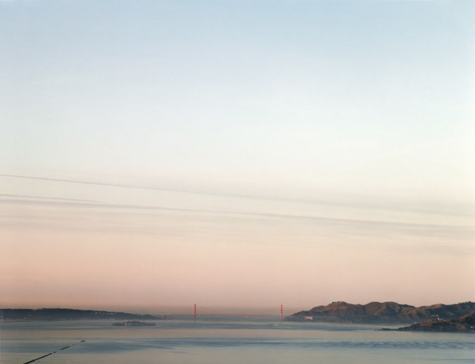 Color photograph of the distant Golden Gate Bridge under a clear pale blue and pink sky