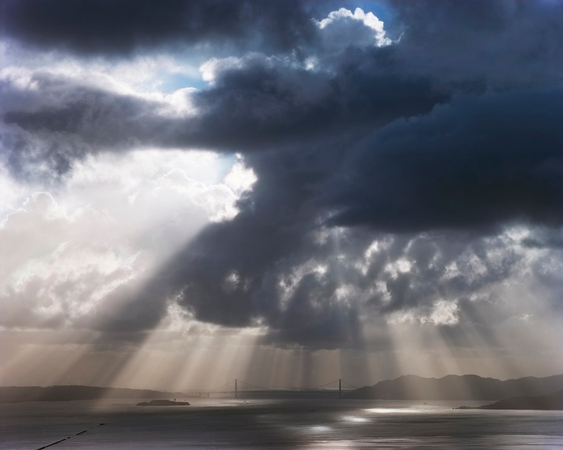 Color photograph of the distant Golden Gate Bridge under stark beams of sunlight coming through dark clouds