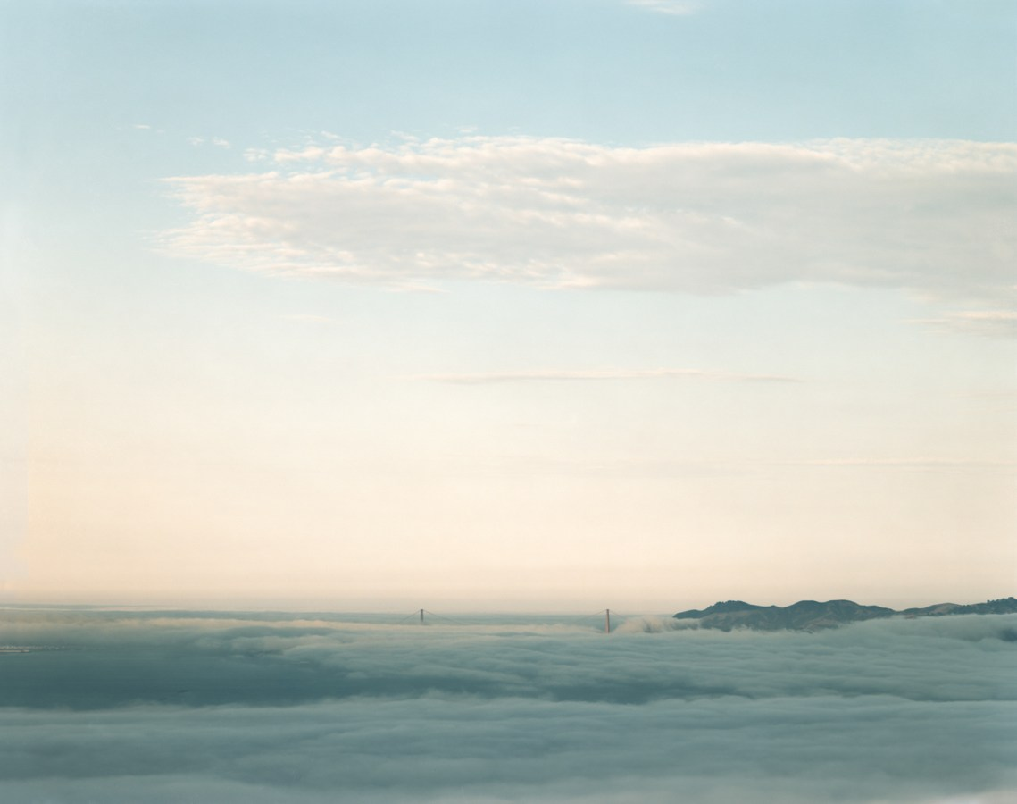 Color photograph of the Golden Gate Bridge on the horizon poking through low fog