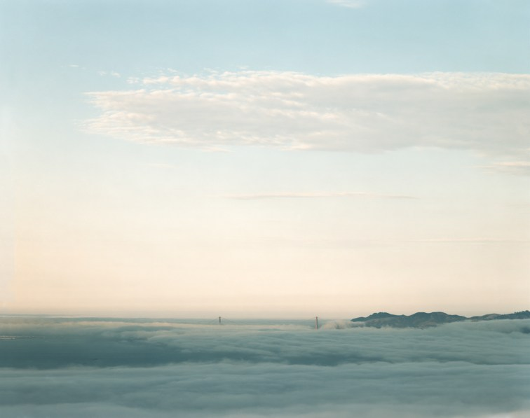 Color photograph of the Golden Gate Bridge on the horizon poking through low fog