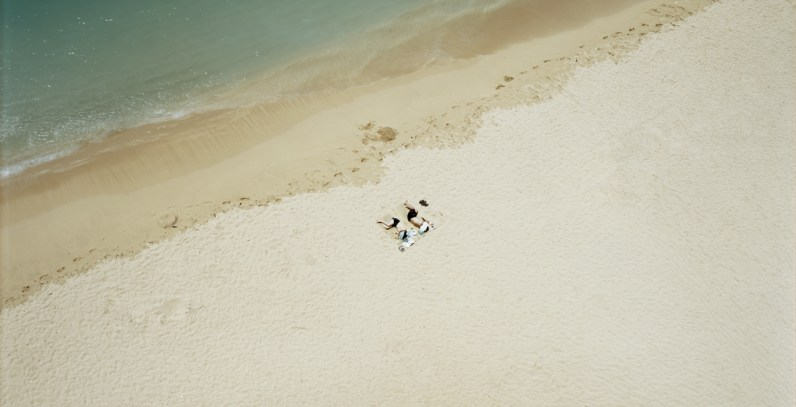 Color aerial photograph of two people curled up on a sandy beach near the waterline