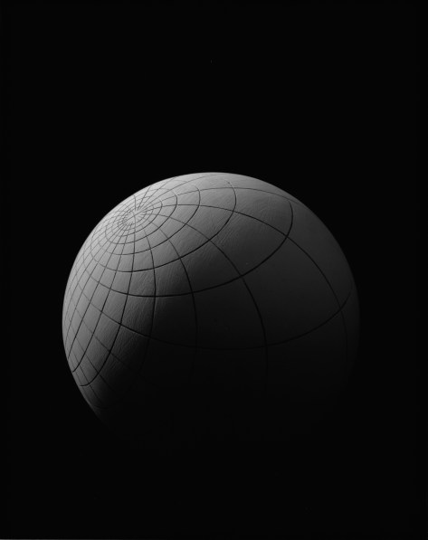 Black-and-white photograph of an orb lit from the top left with grid engravings