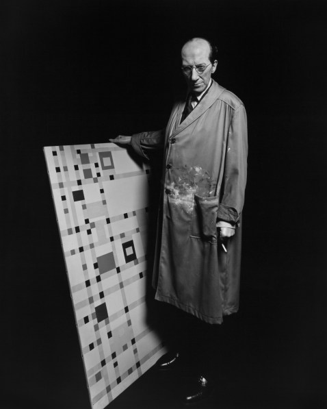 Black-and-white frontal portrait of a wax figure of a man in a long artist's smock with an abstract painting of small squares propped upright in one hand