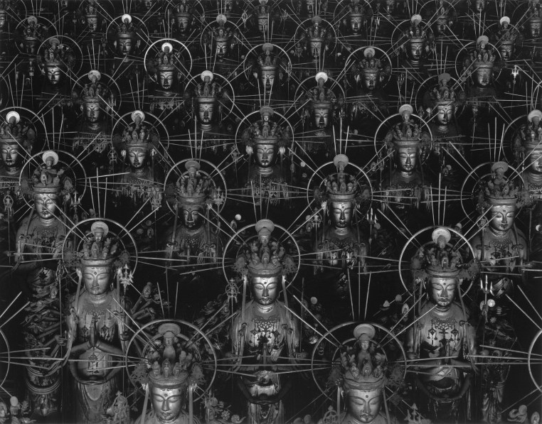 Black-and-white photograph of receding rows of Buddha statues arranged in an alternating pattern