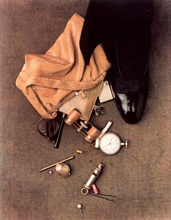 Colored photograph of an assortment of spilled items including a pocket watch and whistle on the floor next to a shiny black shoe