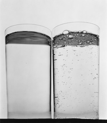Black-and-white photograph of two plain cylindrical glasses, one filled with still water and the other bubbling
