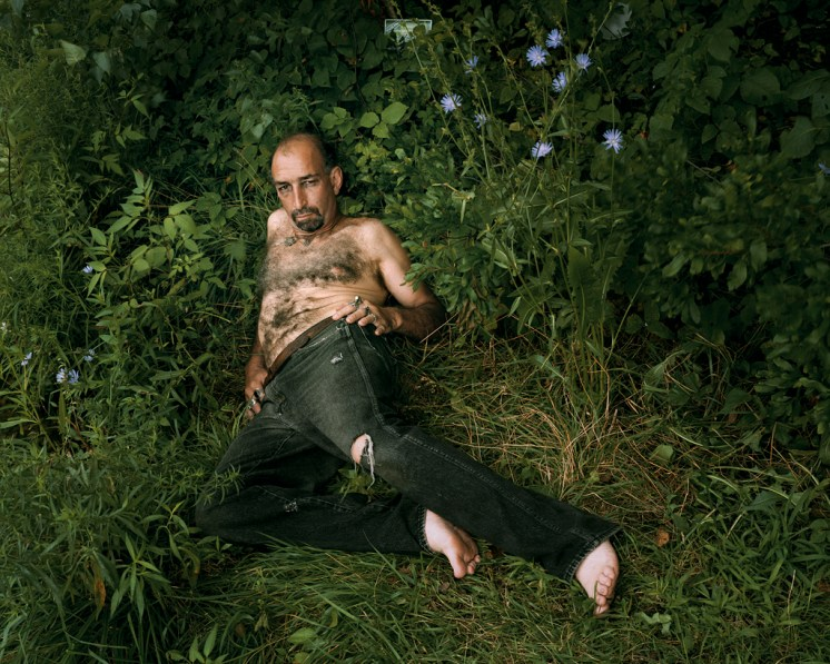 Color photograph of a shirtless man reclining in a patch of long grass
