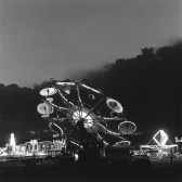 A black and white photograph of an illuminated carnival ride at dusk against a cloudy sky.