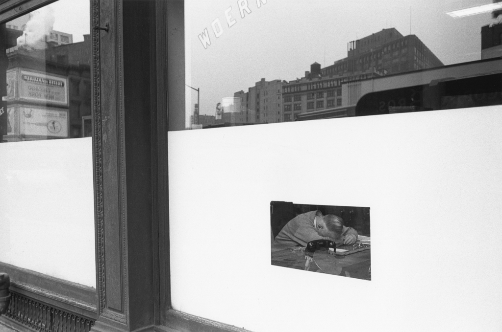 Black-and-white photograph of a man with laying his head on a table through the window of a storefront