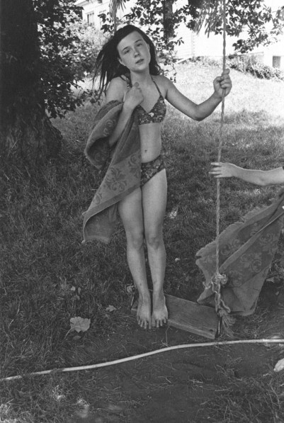 Black-and-white photograph of a girl in a bathing suit standing on a rope swing