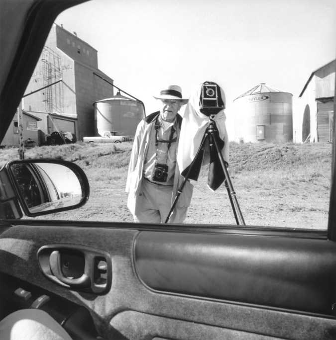 Black and white photograph out the window of a car of a man with a camera on a tripod
