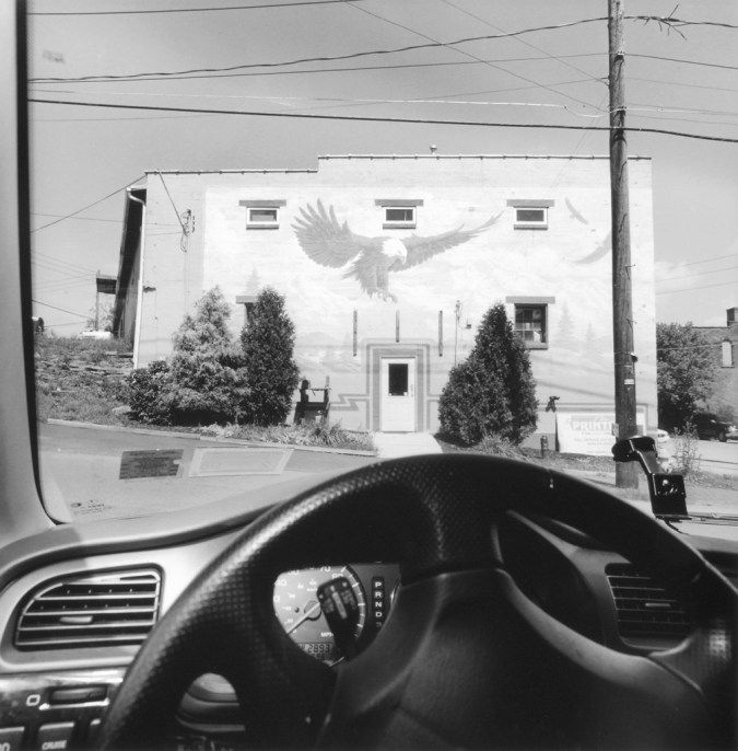 Black and white photograph out the window of a car of a building with an eagle painted on it