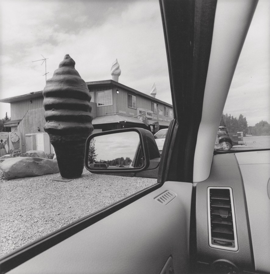 Black and white photograph out the window of a car of a large fake ice cream cone roadside attraction
