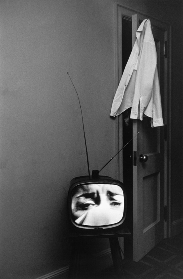 Black-and-white photograph of a television with a crying face on screen and a shirt hanging from an open door