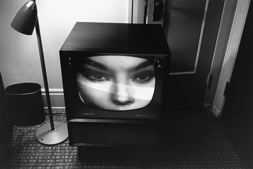 Black-and-white photograph of a television with an up close image of a womans face on screen