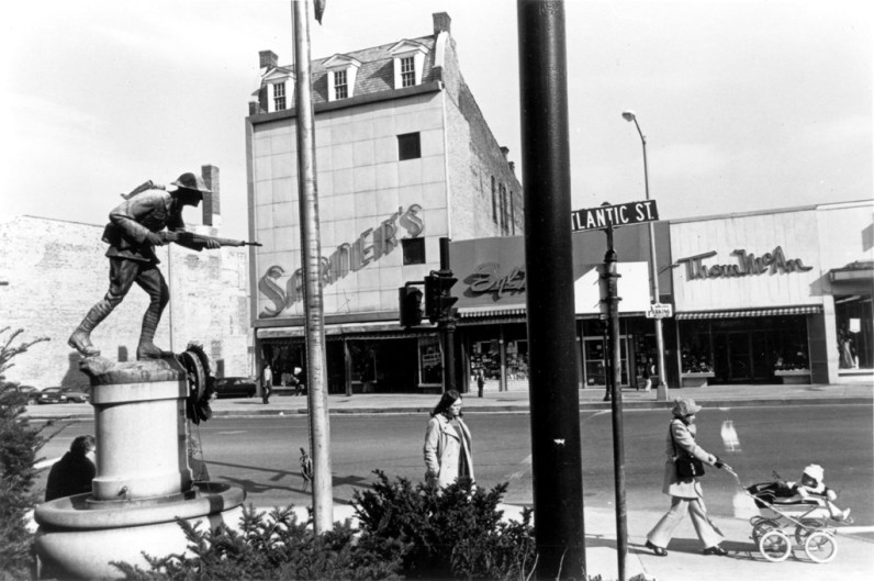 Black and white photograph of a monument of a man holding a gun and people walking in the direction the gun is pointed