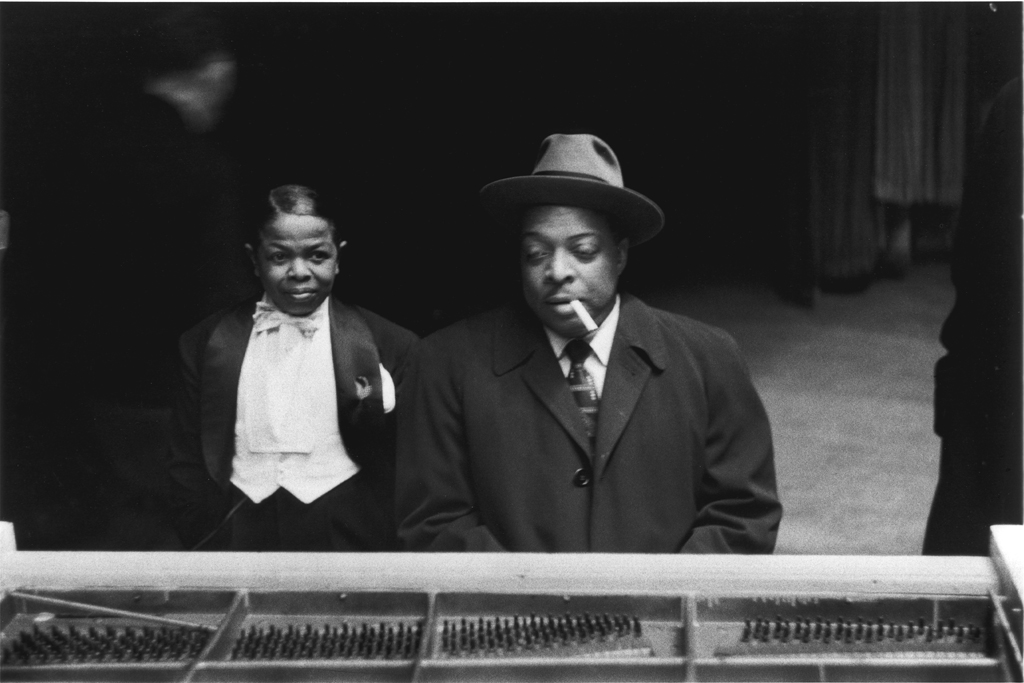 Black and white photograph of a man smoking a cigar and a boy at a piano