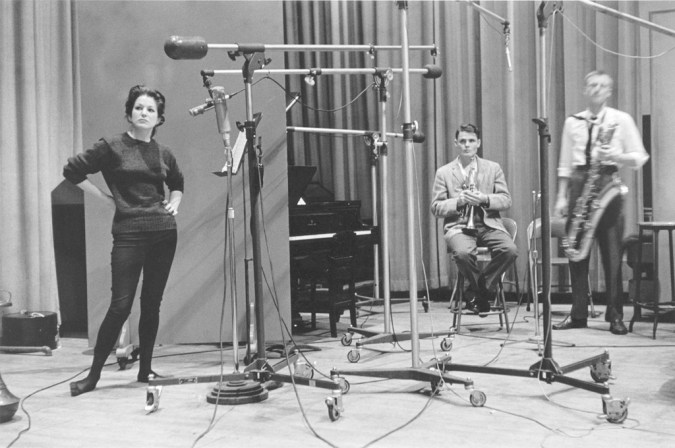 Black and white photograph of three figures with instruments and audio equipment