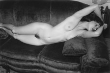 A black and white photograph of a nude woman laying on a sofa